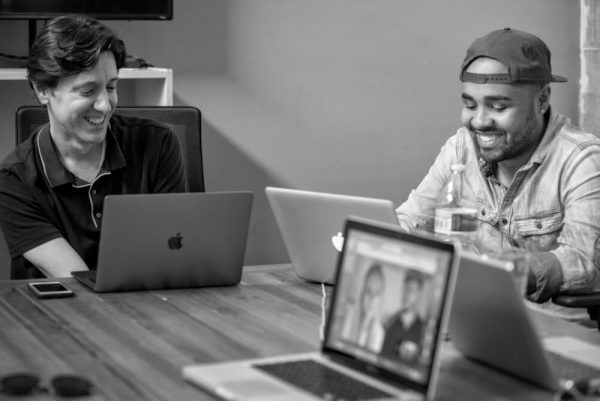 Two screenwriters laughing while writing