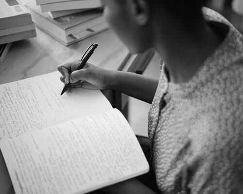 Black woman writing in a notebook