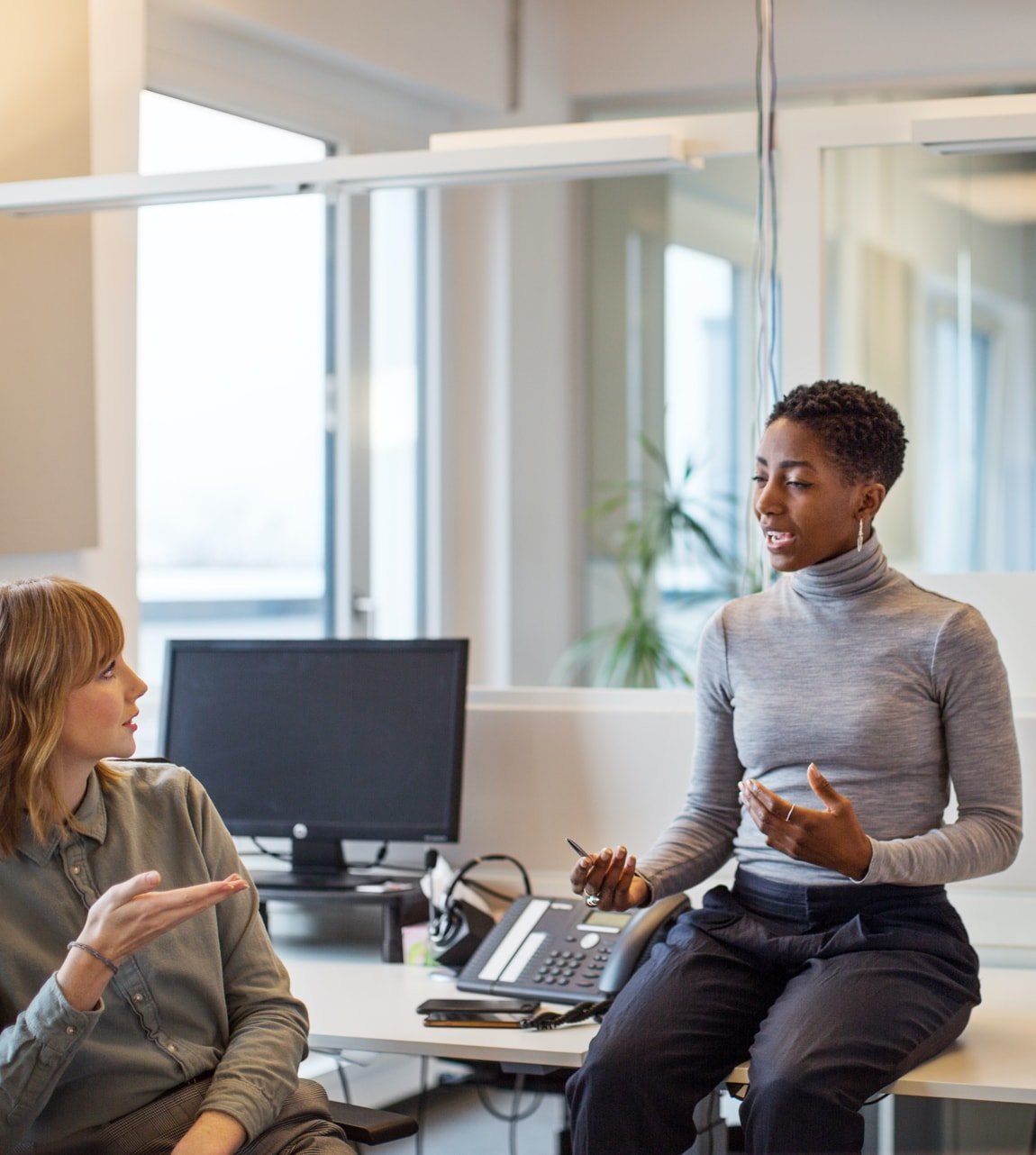 Black-woman-sitting-on-work-table-talking-to-white-woman-content-photo