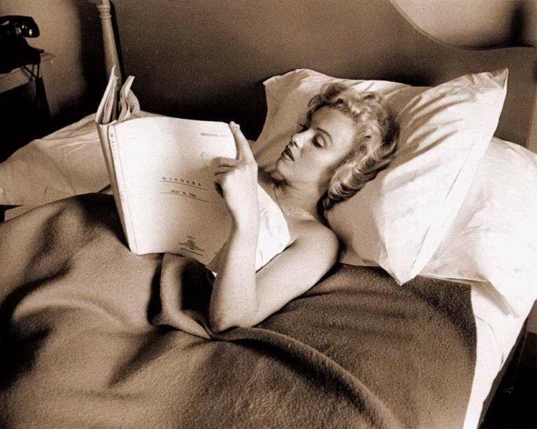 Marilyn Monroe reading a screenplay in bed