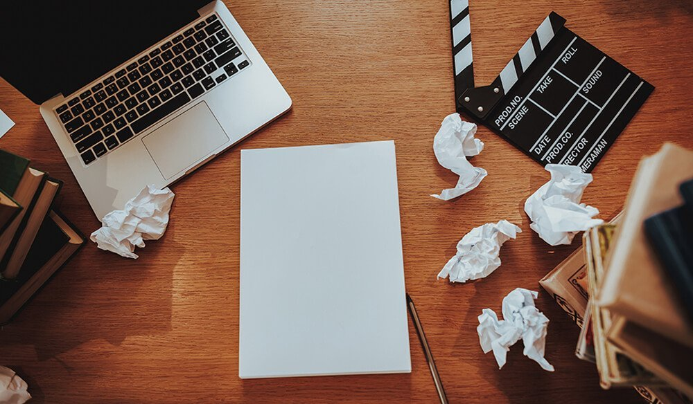 A blank page surrounded by crumpled up pieces of paper and a film clapperboard
