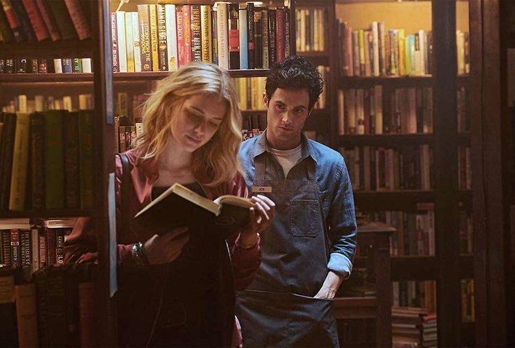 man staring at woman reading