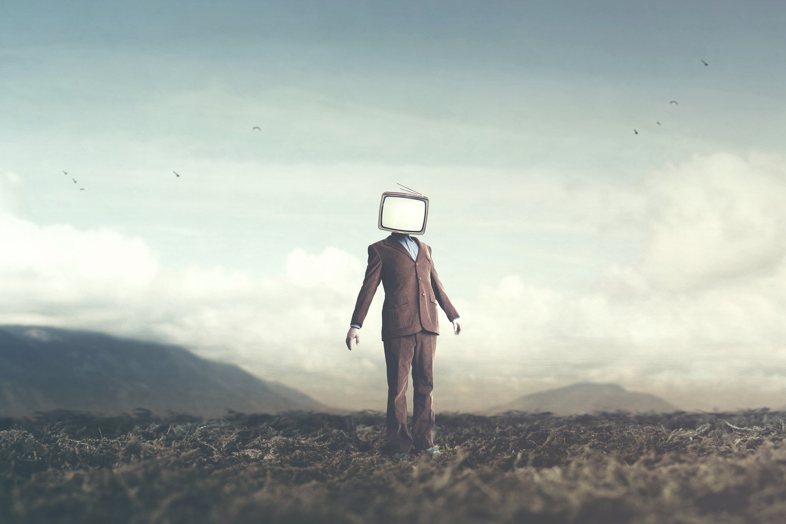 surreal picture of a man with a TV on his head
