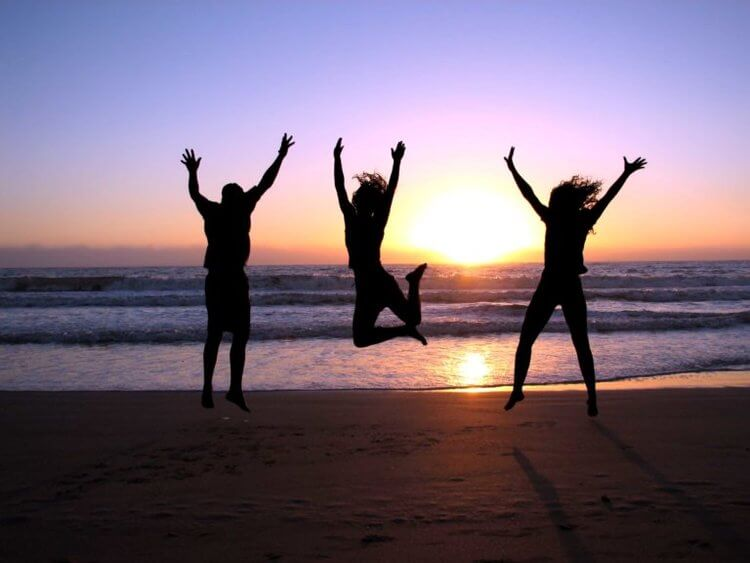 people jumping in the air at the beach
