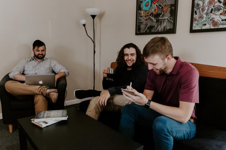 three guys talking and sitting